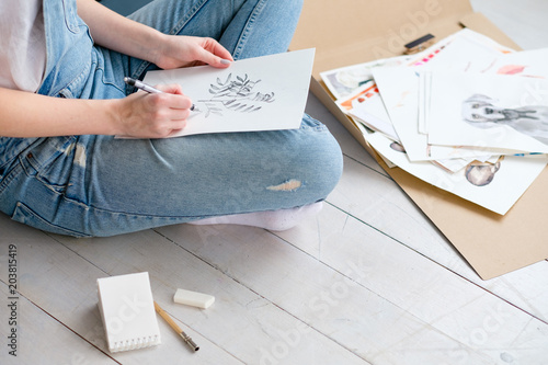 Fototapeta artistic lifestyle. creation inspiration and self expression. drawing leisure. girl in a boiler suit sketching a picture at home