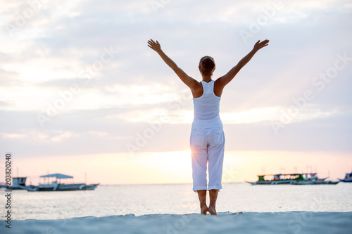 Fototapeta A woman is doing yoga exercises at the sunset on Boracay island, Philippines
