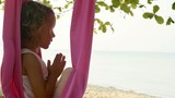 Little cute child girl doing yoga exersice with hammock in the beach. - 203824445
