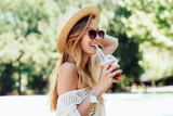 Summer photo of lovely cheerful woman in sunglasses, drinking a fresh cocktail from straw, while walking outside. Dressed in stylish clothes, in hat. - 203839442