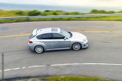 Sporty Hatchback Car Drives Along Curvy Coastal Road in California
