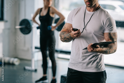 Wall mural cropped shot of male personal trainer looking at timer and young sportswoman exercising with dumbbells behind at gym