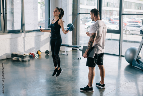 Wall mural male personal trainer looking at sportswoman exercising with jump rope at gym