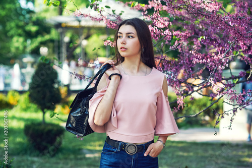 Portrait of a young beautiful girl, model posing on a European city street, against the background of flowering trees Girl dressed in jeans and a blouse , holding a bag. Women's fashion concept.