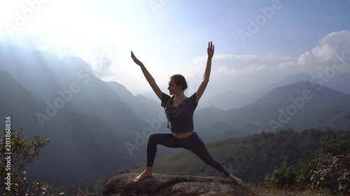 Poster Yoga. Woman exercising and warming up on mountain cliff