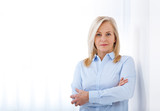 Successful business woman looking confident and smiling. business woman in blue shirt looking friendly into camera standing near window in office - 203874864