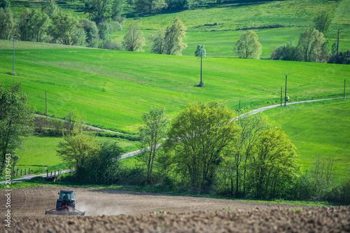 Aluminium Trekker Tractor plowing field and beautiful landscape, France