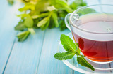 Mint tea in a glass cup on a wooden background - 203877688