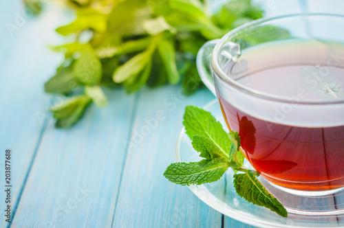 Nowa herbata w szklanej filiżance na drewnianym tle