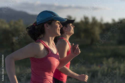 Friends woman talking and smiling outdoors run training in spring day