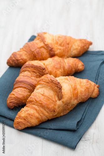 Fototapeta Tasty buttery croissants on old wooden table.