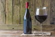 Quadro Bottle and glass of red wine on rustic background with copy space
