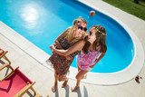 Happy girls smiling by the pool and enjoying summer - 203897253