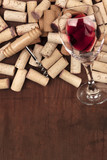 Glass of red wine with corks and corkscrew on a dark rustic background with copy space - 203897280