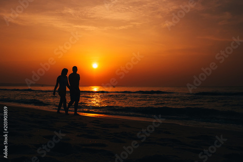 Plexiglas Strand silhouettes of a couple in love on the beach by the sea on the background of orange sunrise