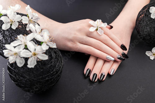 Plexiglas Manicure Black and silver manicure with cherry blossom on black background. Woman with black nails surrounded with white flowers