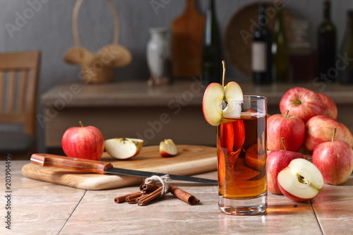Fototapeta Glass of apple juice and ripe pink apples on a kitchen table