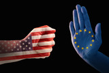 trade conflict, fist with USA flag against a hand with European flag, isolated on a black background - 203907053
