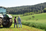 couple of farmers looking at a field - 203908626