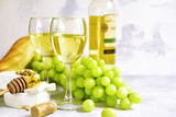 Two glasses of white wine,cheese and grapes. - 203911060