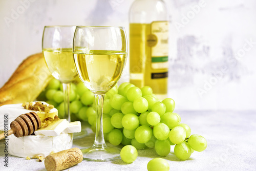 Fototapeta Two glasses of white wine,cheese and grapes.