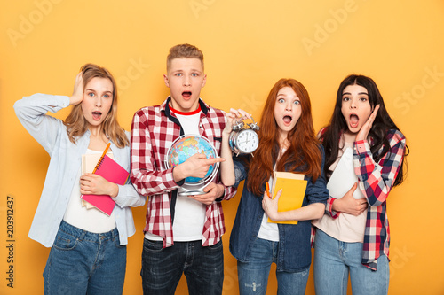Group of shocked school friends showing alarm clock - 203912437