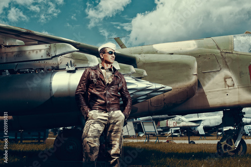 fototapeta na ścianę Fighter Pilot with sunglasses in full flight gear standing at the front of his jet