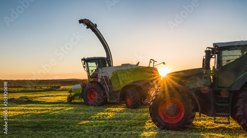 Foto Spatwand Trekker Tractor working agicultural machinery in sunny day