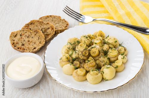 Fototapeta Pickled mushrooms, mayonnaise, pieces of bread, yellow napkin, fork