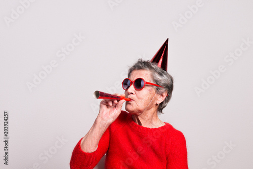 Portrait of a senior woman in studio on a gray background. Party concept. - 203924257