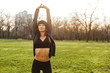 Quadro Image of attractive sportswoman in tracksuit, raising arms and stretching body on grass