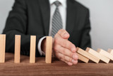 Businessman stopping domino effect with his hand. Security and insurance concept - 203932286