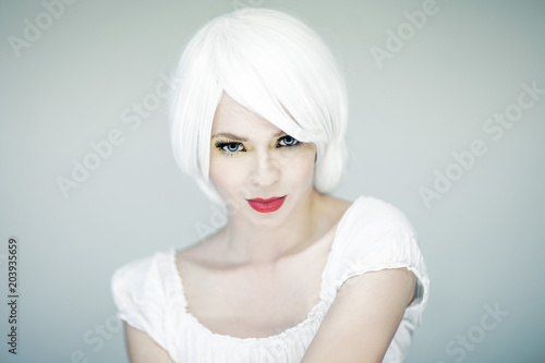 Beautiful young woman in white with perfect pink make up fashion portrait, white hair, looking into camera