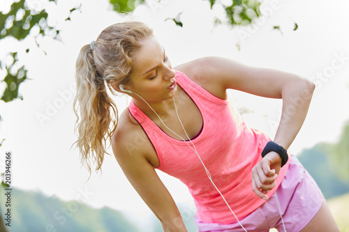 Junge Frau schaut auf ihre Smartwatch - 203946266