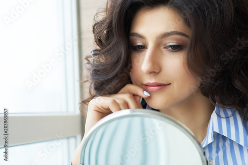 Reflection of the hairstyle of the female client in mirror. Concept of fashion and beauty. Beautiful brunette with lush hair looks at the result of the work of the stylist.