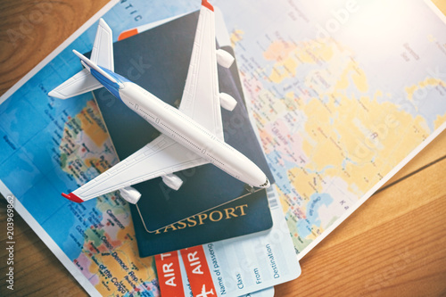 Fototapeta Plane model with world map, passports and tickets as airplane traveling and tickets booking concept