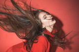Lady with make up waving her hair. Woman with stylish makeup and long hair posing in total red outfit. Fashion concept. Girl on mysterious face in red formal jacket, red background.