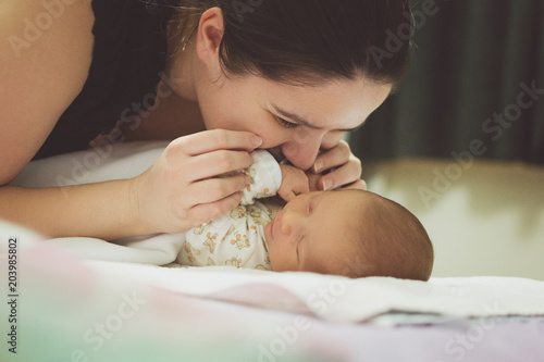 Happy mother kissing her sleeping newborn baby