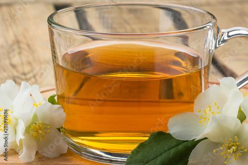 zielona herbata i jaśminowe kwiaty, herbata z jaśminem, kubek herbaty na drewnianej desce