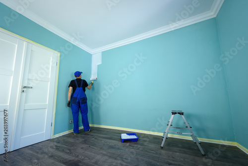 Man in a working overall is painting the wall in white color