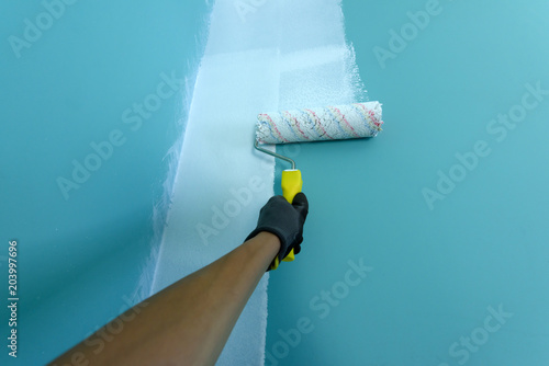 Hand with painting roller paint the wall in white color