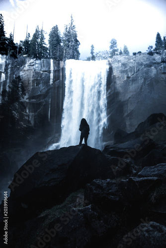 girl standing in front of water fall