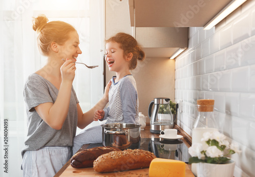 preparation of family breakfast. mother and child daughter cook porridge in morning