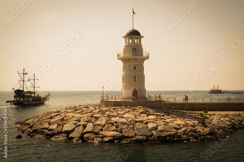 Fotobehang Vuurtoren Lighthouse in Alanya, Turkey. Ships are walking along the Mediterranean Sea near the Lighthouse