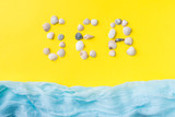 The concept of summer vacation. Seashells yellow background Blue scarf imitation sea Text of shells SEA
