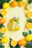 Summer fruits water with lemon, orange, mint and ice in mason jar on yellow. Tropical concept.