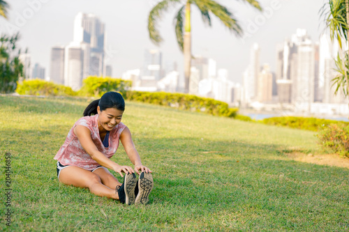Fototapeta Asian woman doing joga exercises outdoors. City landscape on a background