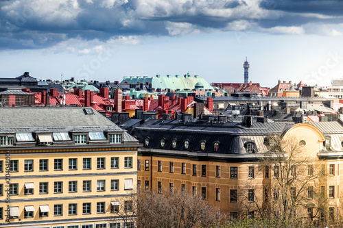 Plexiglas Stockholm Roof tops and old houses in Stockholm city center. Cloudy dramatic dark sky.