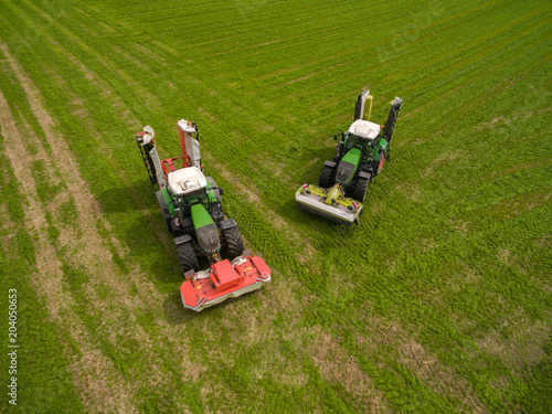 Fotobehang Groene Aerial view of two tractor mowing a green fresh grass field, farmer in a modern tractors mowing a green fresh grass field on a sunny day