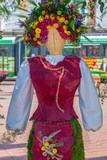 Floral decoration with a wooden statue dressed in a popular costume made of flowers - 204056263